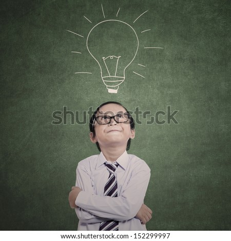 Asian business kid is thinking with hand drawn lightbulb in class - stock photo