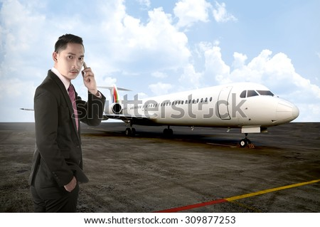 Asian business man calling with his cellphone with plane background - stock photo