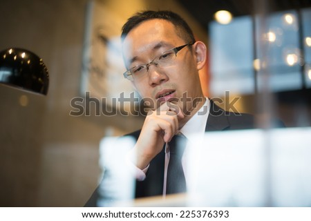 asian business man having coffee while reading ,shot from windows with reflection - stock photo