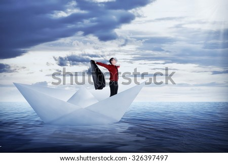 Asian business man open his jacket, sailing on the ocean - stock photo