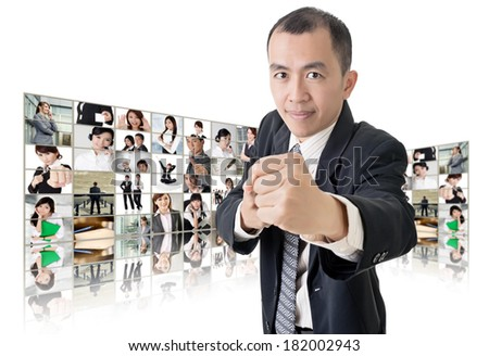 Asian business man or boss standing in front of tV screen wall showing pictures of business concept. - stock photo