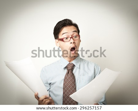 Asian business man reading and stunned with a document. - stock photo