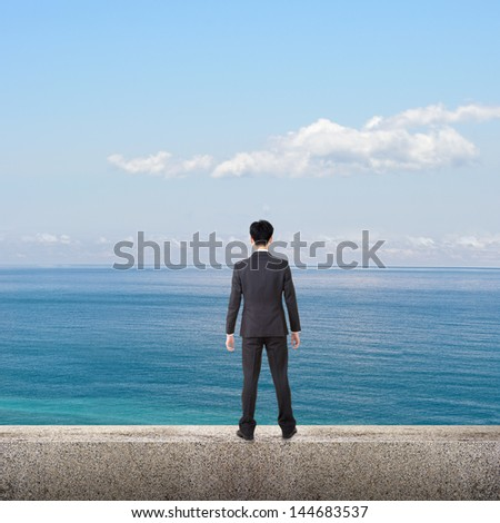 Asian business man stand and look the ocean under blue sky, concept of freedom, life, leisure, future etc. - stock photo