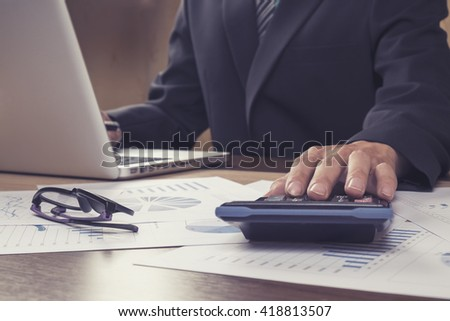 Asian Business man using a calculator to calculate the numbers.Vintage tone - stock photo