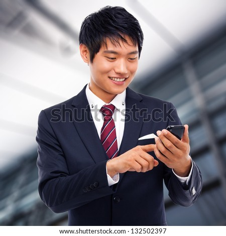 Asian business man with cellphone in business background. - stock photo