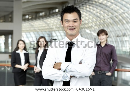 Asian Business man with colleagues in the background out of focus - stock photo