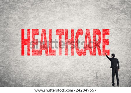 Asian business man write words on wall, Healthcare - stock photo