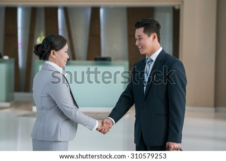 Asian business partner shaking hands to greet each other - stock photo