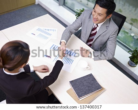 asian business people shaking hands in office, high angle view. - stock photo