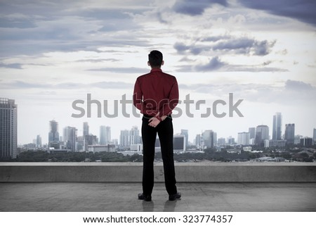 Asian business person, standing on the rooftop, looking the city - stock photo