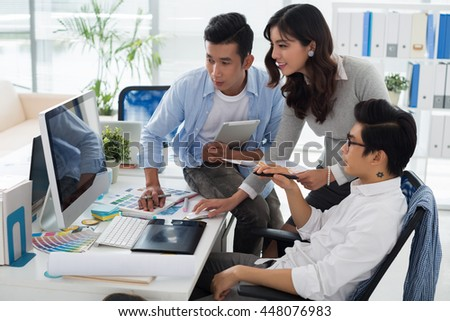 Asian business team gathered in front of computer - stock photo