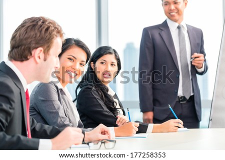 Asian business team in presentation discussing ideas - stock photo