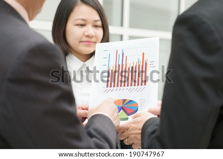 Asian business team meeting. Staff presenting chart to CEO boss over office. Focus on the chart. - stock photo