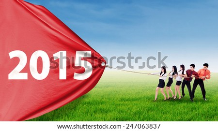 Asian business team pulling number 2015 on a big banner outdoors - stock photo