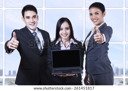 Asian business team showing blank screen on laptop and thumbs up - stock photo