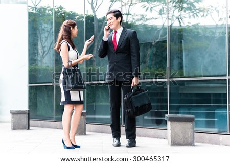 Asian business woman and man telephoning with mobile phone in front of building - stock photo