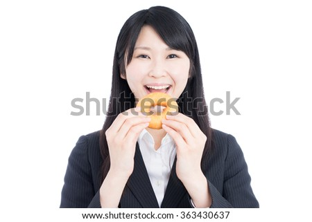 Asian business woman drinking eating a doughnut isolated on white background - stock photo