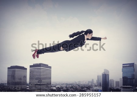 Asian business woman flying over the city - stock photo