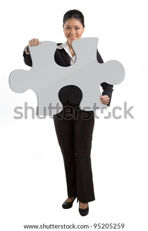 Asian Business woman holding an oversized jigsaw piece. Isolated on white. - stock photo