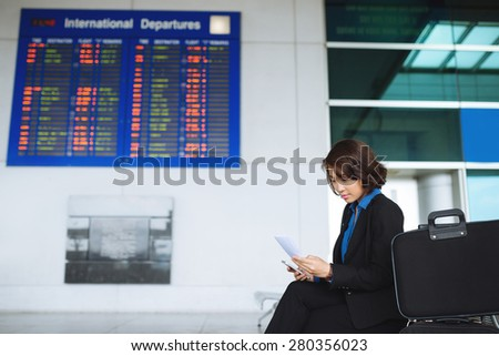 Asian business woman reading information on the plane ticket - stock photo