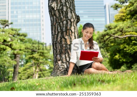 Asian business woman reading using tablet app in Tokyo. Young adult student studying e book with pc touchpad ereader computer or digital tablet in park near Ginza district, downtown of Tokyo, Japan. - stock photo