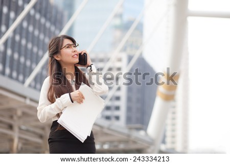 Asian business woman talking smart phone.smile and standing on sidewalk.holding paper and document file. - stock photo