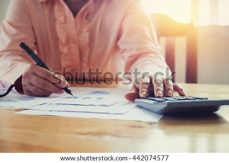 Asian Business woman using a calculator to calculate the numbers vintage tone - stock photo