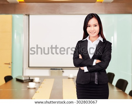 Asian business woman with folded hand smiling with office background - stock photo