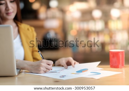 Asian business woman working with document and laptop in office. - stock photo
