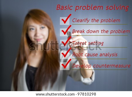 Asian business woman writing Basic problem solving on whiteboard - stock photo