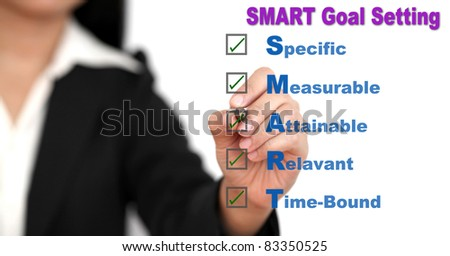 Asian business woman writing SMART Goal setting specific, measurable, attainable, relevant, time on whiteboard - stock photo