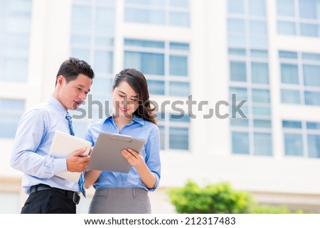 Asian businessman and businesswoman discussing document outside the office - stock photo