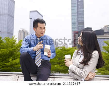 asian businessman and businesswoman talking outdoors. - stock photo