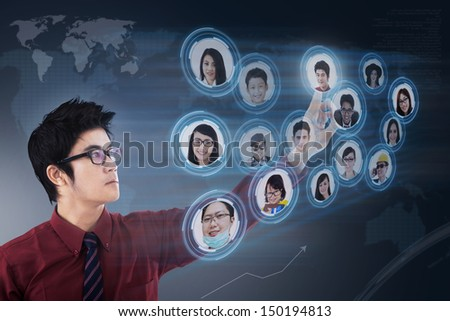 Asian businessman clicking on the social networking map over a digital world map - stock photo