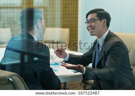 Asian businessman explaining something to his partner - stock photo