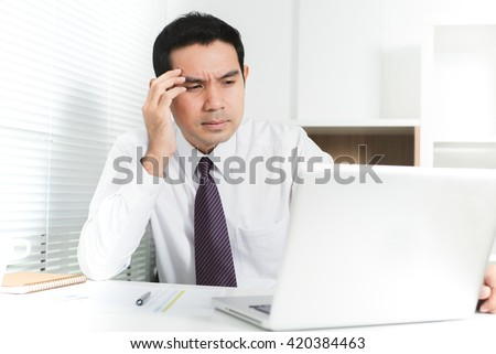 Asian businessman getting stressed (upset) at work, putting his hand on temple - stock photo