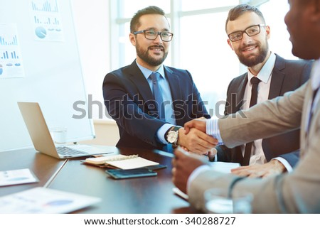 Asian businessman handshaking with partner after negotiation - stock photo