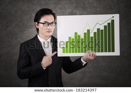 Asian businessman holding a billboard with chart of profits  - stock photo