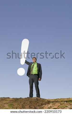 Asian businessman holding exclamation point - stock photo