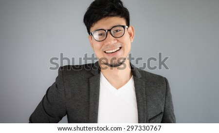 Asian businessman in black suit with grey background. - stock photo