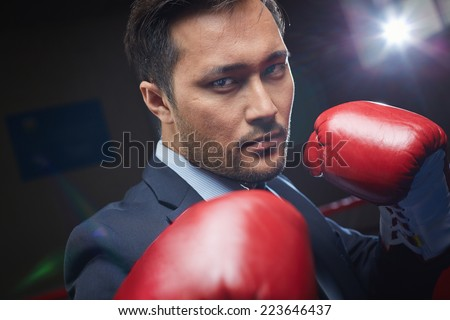 Asian businessman in red boxing gloves looking at camera - stock photo