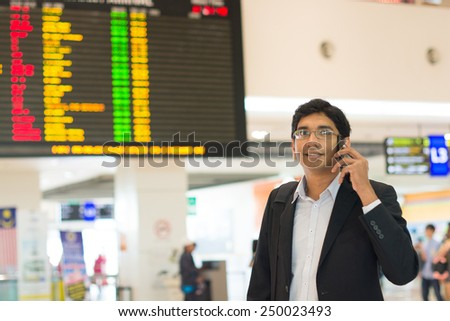 Asian Businessman on the phone during his business travel, at the airport . - stock photo