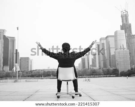 asian businessman opens arms embracing the city, black and white. - stock photo