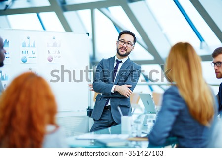 Asian businessman presenting ideas to colleagues - stock photo