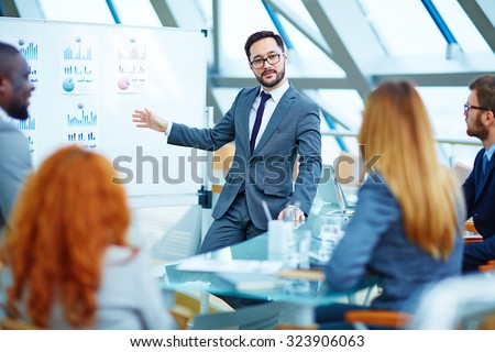 Asian businessman presenting review of financial data to colleagues - stock photo
