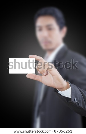 Asian businessman pushing white name card. - stock photo