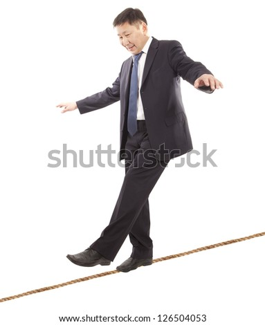 Asian businessman rope-walker. Isolated on white background - stock photo