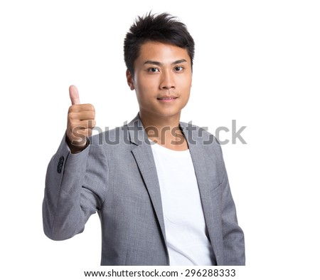 Asian businessman showing thumb up gesture - stock photo