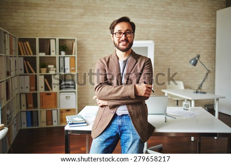 Asian businessman standing by his desk in office - stock photo