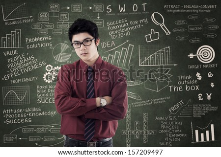 Asian businessman standing over success formula. Shot in the class - stock photo